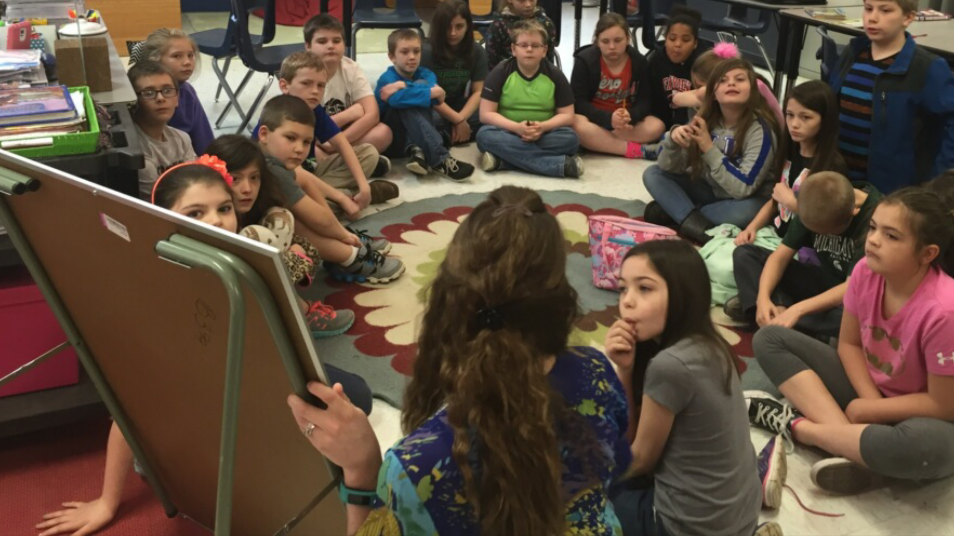 Mrs.Pridemore sitting in the floor discussing a story with students.