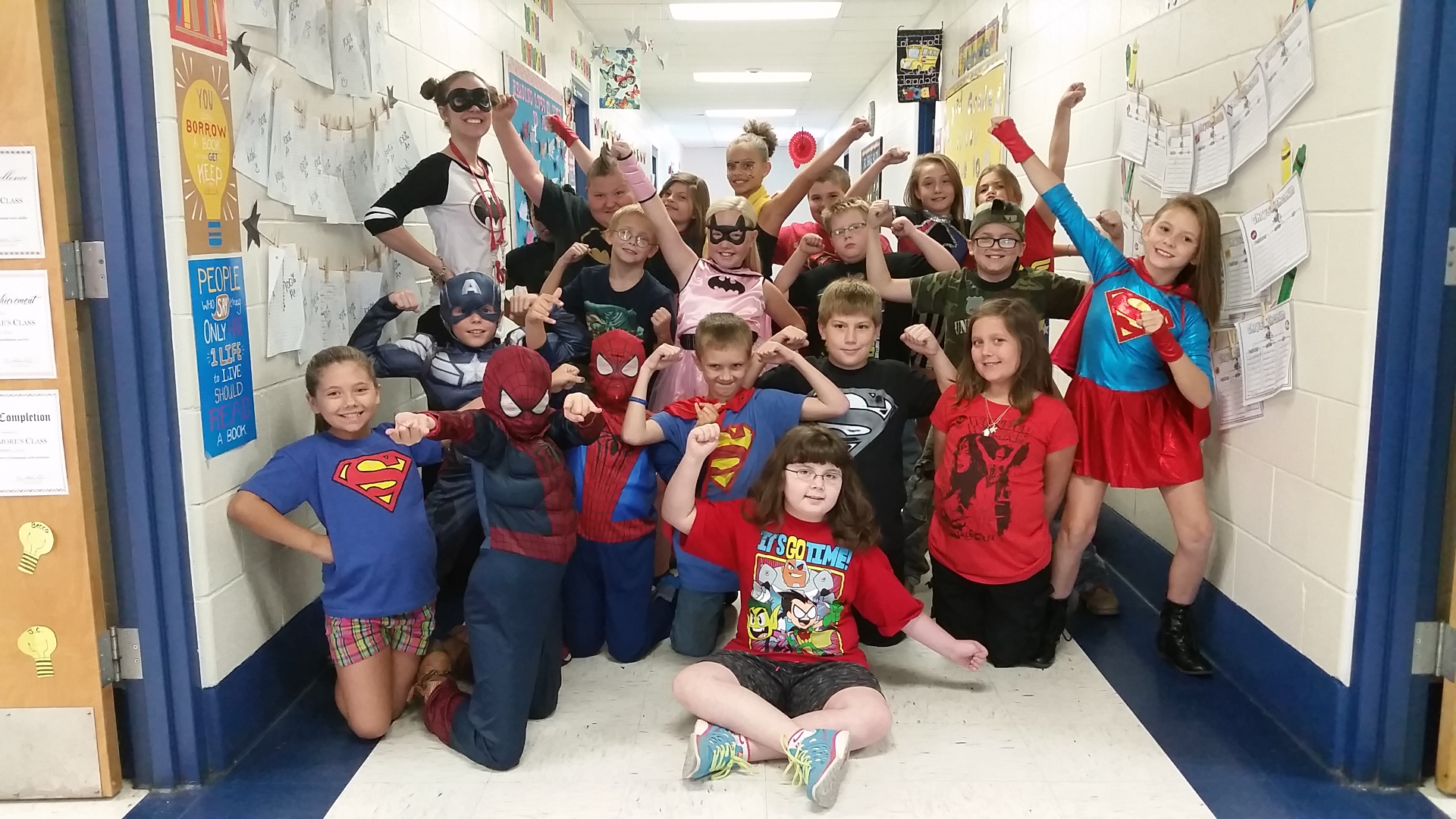 Mrs.Pridemore posing in the hallway with her stuents dressed as super heros.